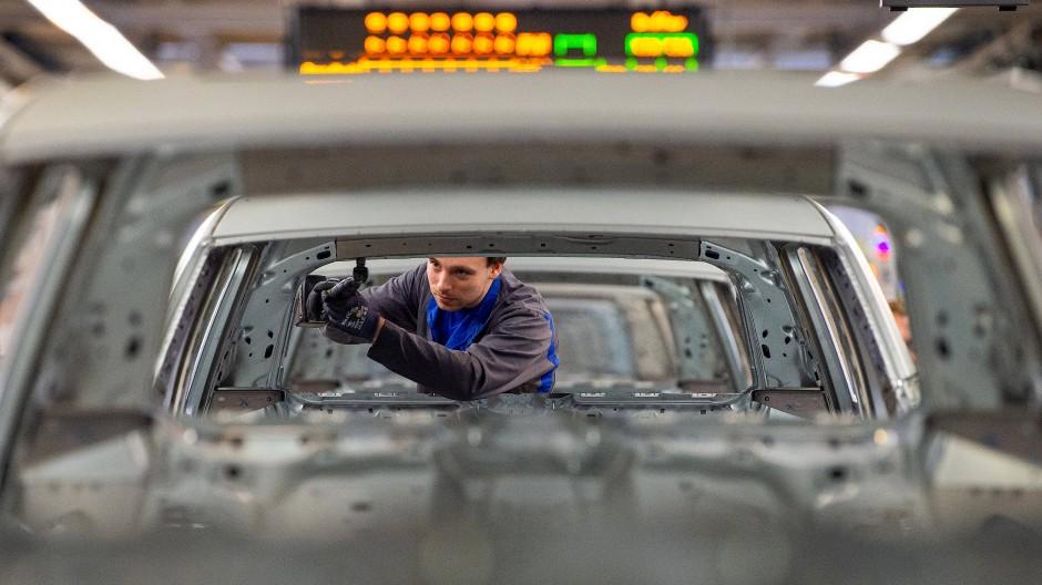 Ein Mitarbeiter schraubt im Karosseriebau im VW Werk in Wolfsburg an einem Volkswagen.