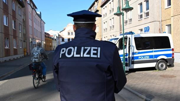 Neun Polizisten aus Cottbus posieren vor rechtsextremem Graffito
