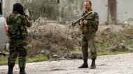 Ein syrischer Soldat macht im syrischen Daraa ein Foto von einem Kameraden, der mit einer russischen Panzerbüchse vom Typ RPG-7 posiert.