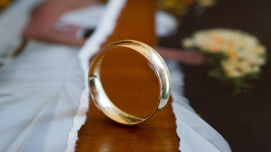 Auf einem Tisch liegt ein zerrissenes Hochzeitsfoto und ein Ehering.