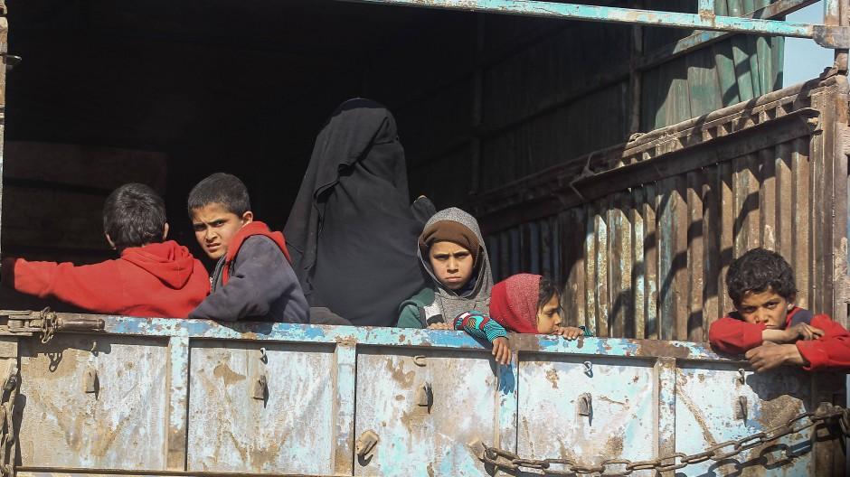 Frauen und Kinder fahren auf einem Lastwagen eines Konvois, der Zivilisten und Familienangehörige von IS-Kämpfern in ein Zwischenlager evakuiert. (Symbolbild)