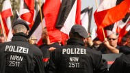Polizisten stehen vor rechtsextremistischen Demonstranten in der Dortmunder Innenstadt.