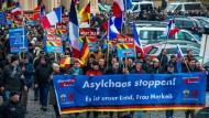 """AfD-Demonstration in Schwerin: """"Asylchaos stoppen"""" steht auf einem Transparent."""