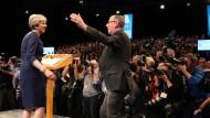 Unter Beobachtung: Theresa May wird nach ihrer Rede von ihrem Ehemann beglückwünscht, während Dutzende Kameras auf sie gerichtet sind.