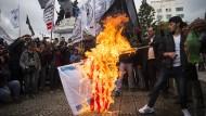 Demonstranten in Gaza zünden am Mittwoch eine israelische und amerikanische Flagge an.