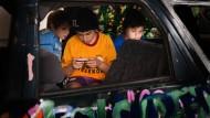 Jungs sitzen im Auto und spielen auf dem Handy im Kasseler Freestyle Sportprojekt.