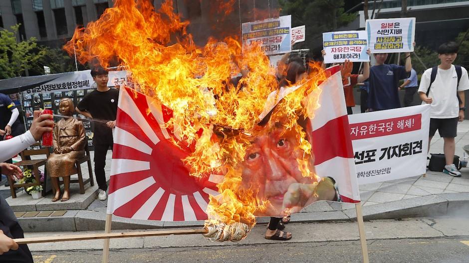 Ein Bild von Japans Ministerpräsident Abe wird während einer Demonstration in Südkorea verbrannt.
