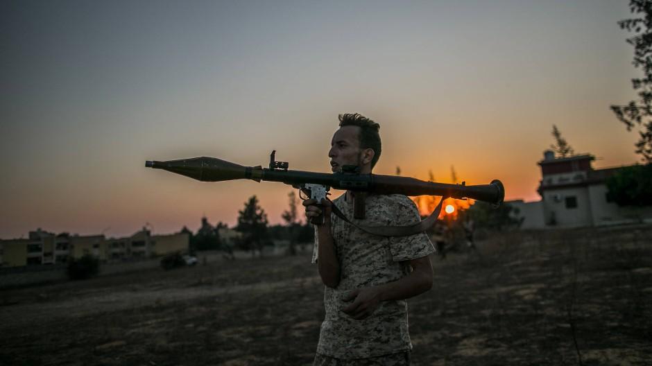 25.08.2019, Libyen, Tripolis: Ein Kämpfer der international anerkannten Regierung nimmt während der Zusammenstöße mit den Truppen der Libysch-Nationalen Armee (LNA) an der Frontlinie Stellung.