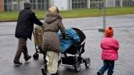 Flüchtlinge gehen im November 2015 im schleswig-holsteinischen Boostedt über das Gelände der Erstaufnahmeeinrichtung.