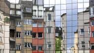 Wohnhäuser in der Kölner Innenstadt spiegeln sich in einer Glasfassade.