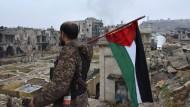 Ein syrischer Soldat steht am Dienstag mit der Flagge seines Landes am Stadtrand von Aleppo