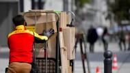 Ein Mitarbeiter der Deutschen Post bei der Zustellung: Den Streit über die Arbeitsbedingungen wird die Reform des Postgesetzes nicht lösen.