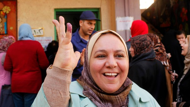 Woman shows her ink-stained finger after casting her vote in a referendum on Egypt's new constitution at a polling station at a school in Alexandria