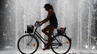 Ungestört Fahrrad fahren: Eine Frau fährt an einem Brunnen im Frankfurter Stadtteil Sachsenhausen vorbei.