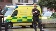 Manchester: Bewaffnete Polizeibeamte stehen nahe eines Einkaufszentrums vor einem Krankenwagen.