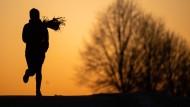 Eine Frau joggt vor dem Sonnenaufgang.
