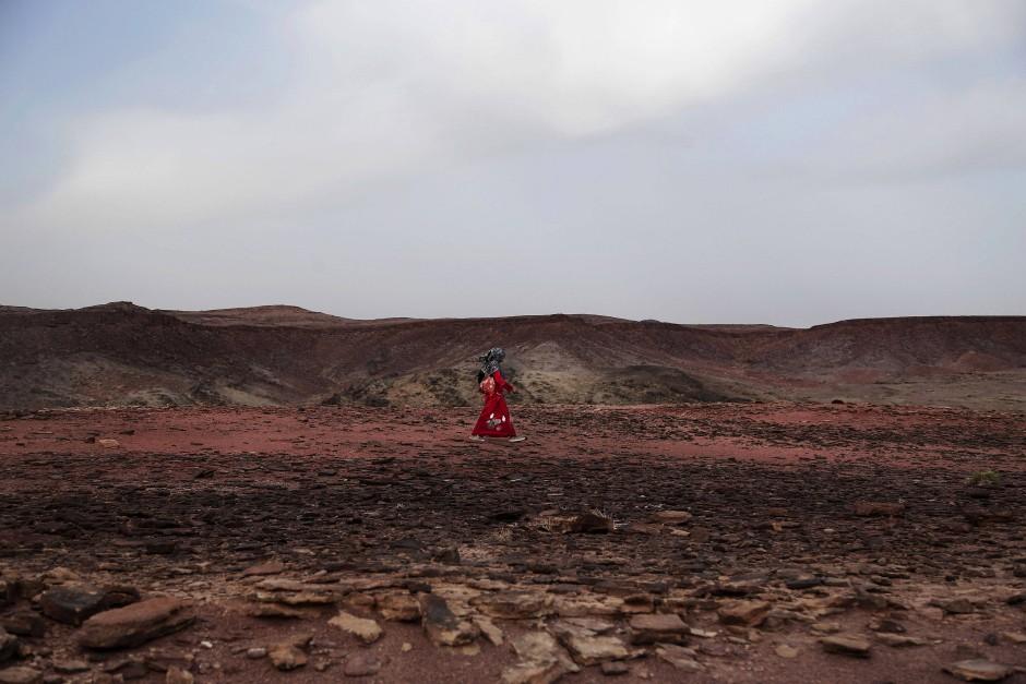 Umm Yasser läuft mit sicheren Schritten über die rote Erde des Trails.