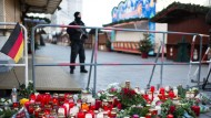 Ein mit einer Maschinenpistole bewaffneter Polizist steht am Anschlagsort auf dem Weihnachtsmarkt am Breitscheidplatz in Berlin.