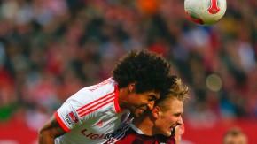 Munich's Dante challenges FC Nuremberg's Polter during their German Bundesliga first division soccer match in Nuremberg