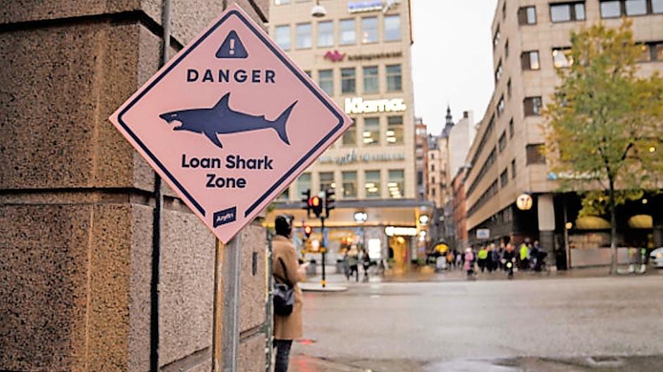 Vor der Klarna-Zentrale in Stockholm: Anyfin warnt mit einem Schild vor Kredithaien.