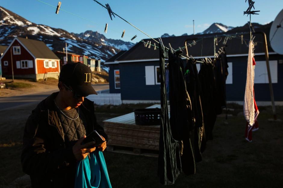 Ein junger Mann hängt Wäsche in der Abendsonne auf.