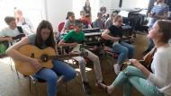 """Der Funke springt über: """"Feuerwerk"""" heißt der Song, den die Siebtklässler der IGS West unter Anleitung von Musikhochschulprofessor Fabian Sennholz (rechts stehend) und seinen Studierenden einüben."""
