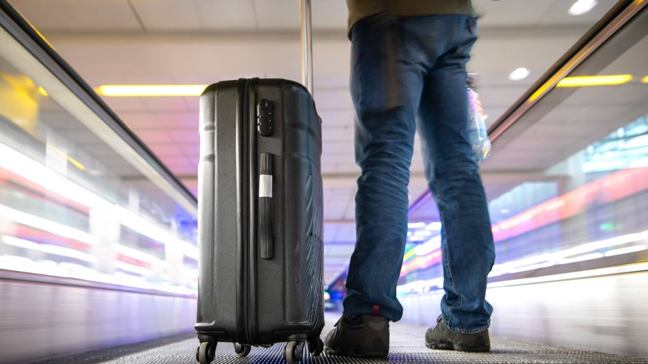 Ein Reisender steht mit seinem Koffer auf einem Fahrsteig