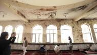 Männer inspizieren am Tag nach dem Anschlag die Räume der betroffenen Moschee.