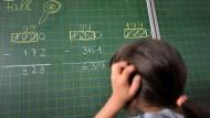 Ein Mädchen der zweiten Klasse einer Grundschule in München steht an der Tafel vor einer Rechenaufgabe.
