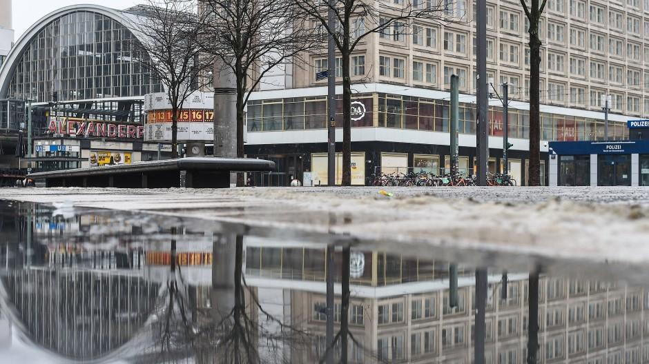 In einer Regenpfütze auf dem fast menschenleeren Alexanderplatz spiegeln sich der S-Bahnhof und die Weltzeituhr.
