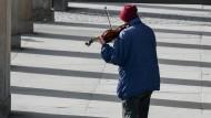 Ein Mann spielt im Kolonnadenhof der Nationalgalerie in Berlin Geige