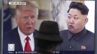 Zwei Männer, eine Gefahr? Ein Mann blickt in Südkorea auf einen TV-Bildschirm mit den Gesichtern von Donald Trump und Kim Jong-un.