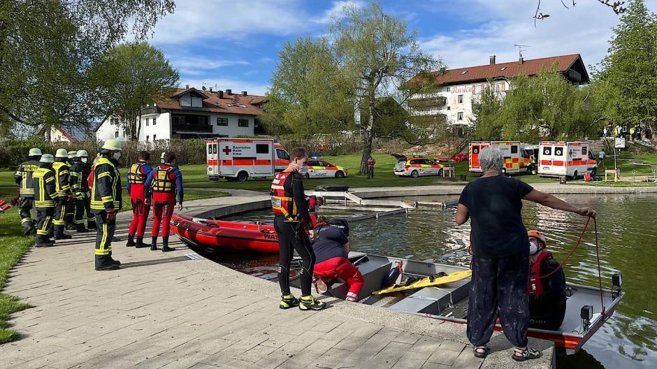 Einsatzkräfte der Feuerwehr und Rettungsdienste stehen an einem Badesee bei Sulzberg im Oberallgäu.