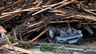Unter einem Holzstapel ist ein Auto begraben - die Schäden zeigen die Wucht des Wassers.