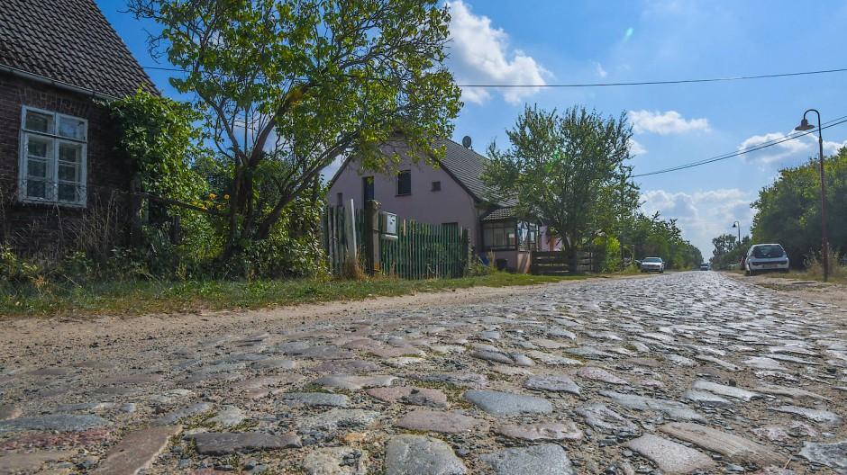 Eine Kopfsteinpflasterstraße führt durch das Dorf Regenmantel, einem Ortsteil der Gemeinde Falkenhagen im Landkreis Märkisch-Oderland. Hier wohnen gerade einmal etwa 80 Einwohner.