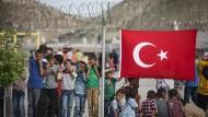 Kinder stehen hinter einem Zaun in einem Flüchtlingslager in der türkischen Grenzstadt Gaziantep (Archivbild).