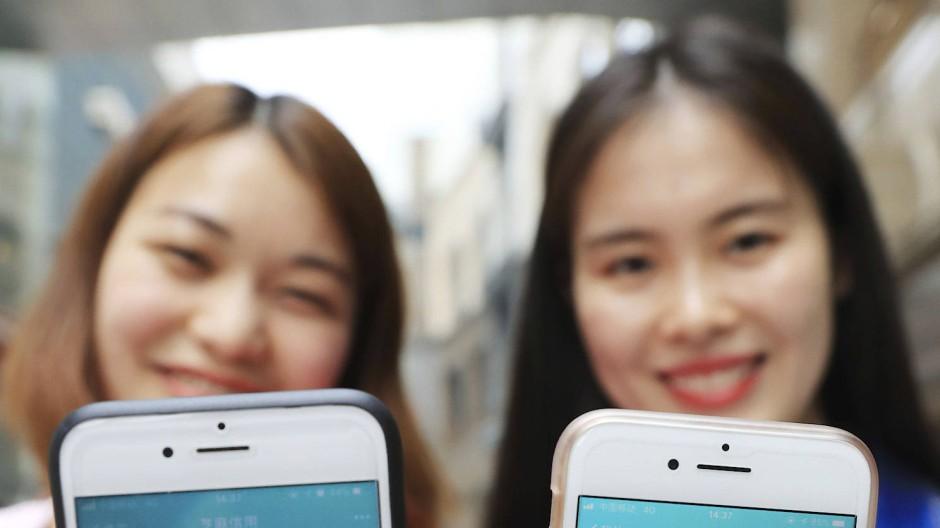 Zwei Frauen zeigen ihr Smartphone mit ihren Sozialkreditpunkten bei dem kommerziellen Anbieter Sesame Credit, der zum Konzern Alipay gehört.