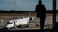 Ein Passagier steht in der Abflughalle und blickt auf eine Lufthansa Maschine auf dem Rollfeld