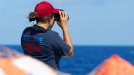 """Ein Besatzungsmitglied der """"Alan Kurdi"""" sucht den Horizont nach in Seenot Geratenen ab (Archivbild vom 29. Juni)"""