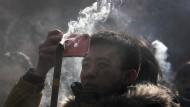 Ein Mann nimmt an Neujahr in Peking ein Foto mit seinem iPhone auf.