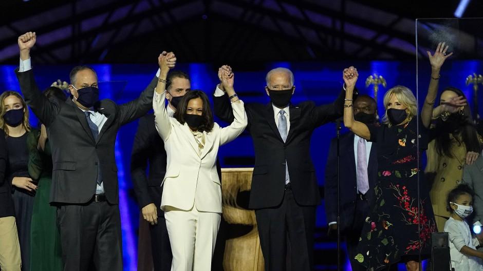 Ein weißer Anzug und ein paar dunkle Anzüge – Kamala Harris und ihr Mann Doug Emhoff (l.) neben Joe und Jill Biden