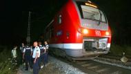 Polizisten stehen neben dem Regionalzug, in dem ein 17-jähriger Afghane mehrere Menschen lebensgefährlich verletzt hat.