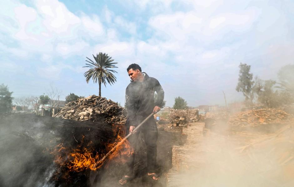 Ein junger Mann bewegt das Feuer mit einer Schaufel, um es nicht ausgehen zu lassen. Die Feuer müssen zehn bis fünfzehn Tage durchbrennen, um Holz in brauchbare Kohle zu verwandeln.