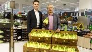 Lidl-Einkaufsleiter Jan Bock (l.) und Dieter Overath, Vorstandsvorsitzender von Transfair, präsentieren faire Lidl-Bananen.