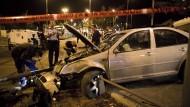 Polizisten untersuchen das Auto, mit dem der Palästinenser offenbar absichtlich in die Haltestelle raste.