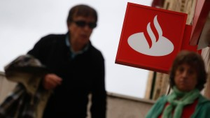 People walk outside a branch of Spain's Santander bank in Madrid