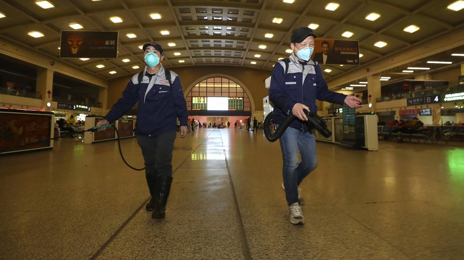 Arbeiter desinfizieren einen Bahnhof im chinesischen Wuhan.