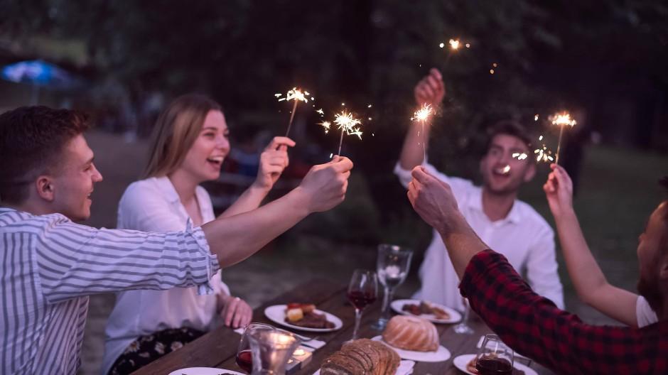 Eine Gruppe Freunde feiert abends mit Kuchen, Wein und Wunderkerzen.