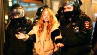Polizisten in Moskau nehmen eine junge Frau fest.