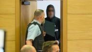 Einer der Angeklagten betritt den Sitzungssaal im Landgericht Bielefeld.